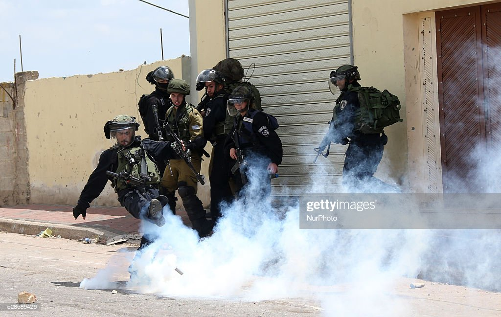 An Israeli soldier throws a tear gas canister towards Palestinian protesters during a protest against the expanding of Jewish settlements in Kufer Qaddom village, near the West Bank city of Nablus. May 6, 2016.