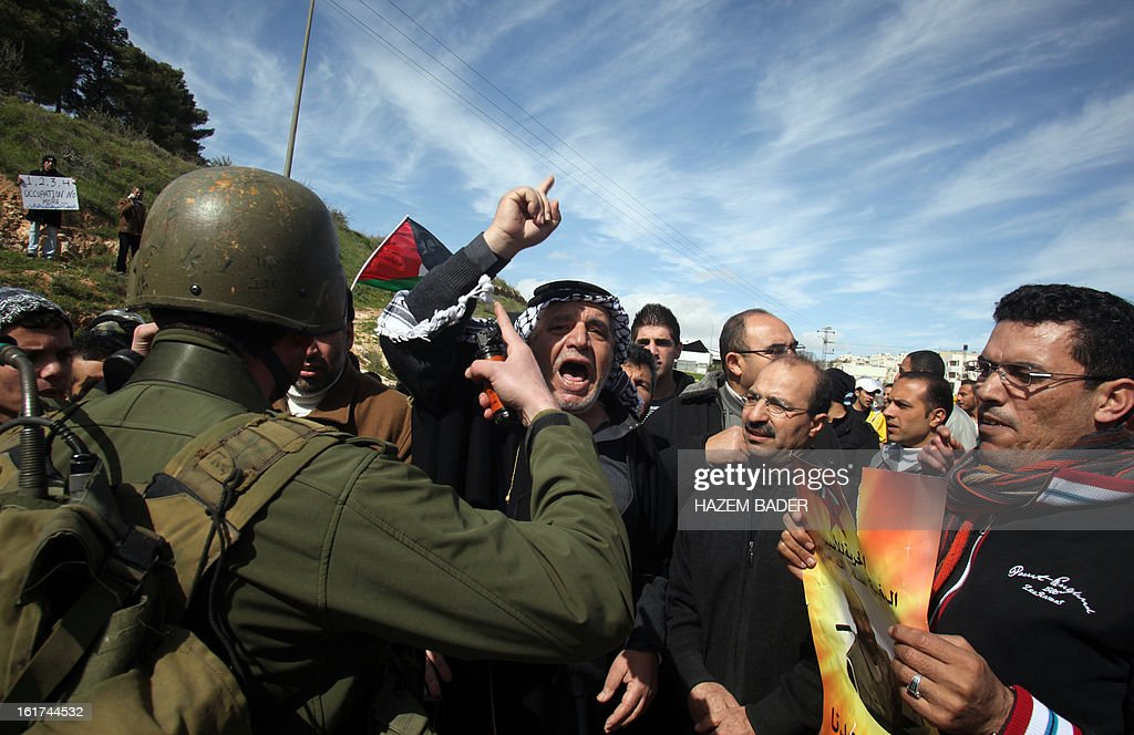 An Israeli soldier tries to break up Palestinian protestors as they demonstrate against the closer of the main southwest entrance of the West Bank city of Hebron, which is situated near the Jewish settlement of Beit Hagai, in the occupied West Bank, on February 15, 2013.