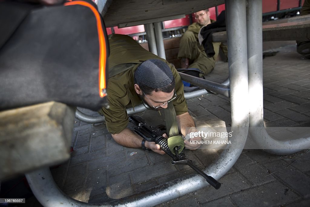 An Israeli soldier uses his mobile phone while taking cover under a bench during a rocket attack from Palestinian militants in the Gaza Strip on 21 November 2012 at Yad Mordechay in southern Israel. Fighting raged on both sides of Gaza's borders Wednesday despite intensified efforts across the region to thrash out a truce to end a week of violence that has cost 136 Palestinian and five Israeli lives. AFP PHOTO/MENAHEM KAHANA