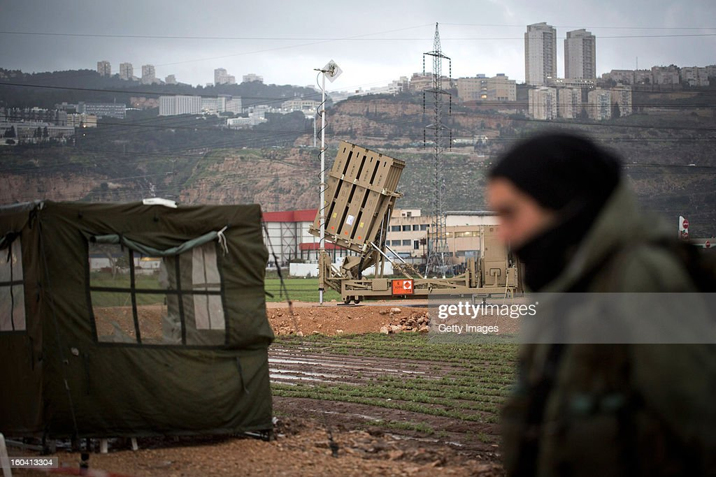 An Israeli soldier walks by an 'Iron Dome' short-range missile defense system positioned near the northern city of Haifa on January 31, 2013 in Israel. The Iron Dome missile defense system is designed to intercept and destroy incoming short-range rockets and artillery shells. Israel remains on high alert to the possibility of Islamic militants getting hold of Syrian missiles and chemical weapons, with reports yesterday that the Israeli air force launched an airstrike on a convoy carrying weapons from Syria to Lebanon on the Syria-Lebanon border.