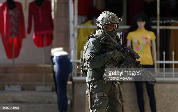 An Israeli soldier walks in front of clothing store during clashes with Palestinian youth in the Palestinian village of alRam between Jerusalem and...