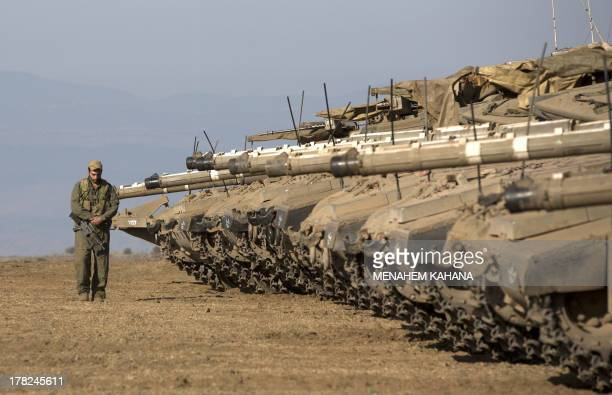 An Israeli soldier walks next to Merkava tanks stationed in a deployment training area in the Israeliannexed Golan Heights near the border with Syria...