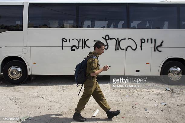 An Israeli soldier walks past a bus on which suspected Jewish vandals painted a graffiti reading in Hebrew 'Gentiles in the land are enemies' on...