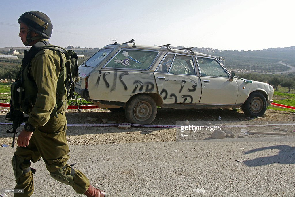 An Israeli soldier walks past a car which was believed to be vandalised by Jewish extremists with graffiti reading in Hebrew: 'leave', in the village of Mansheya south of the West Bank city of Bethlehem on January 4, 2013.