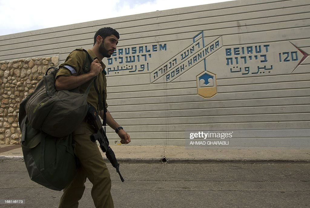 An Israeli soldier walks past a sign indicating the direction and distance to the Lebanese capital Beirut and to Jerusalem at the Israel-Lebanon border crossing in Rosh Hanikra, on May 6, 2013.
