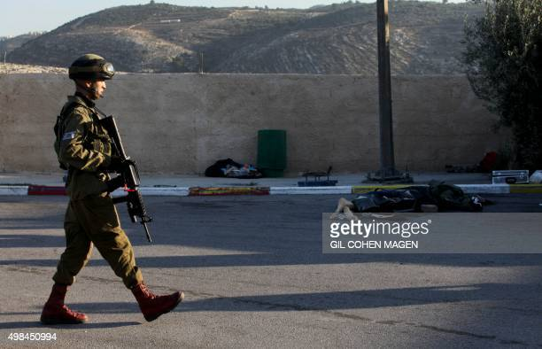 An Israeli soldier walks past the body of a Palestinian assailant who carried out a stabbing attack against two Israeli soldiers killing one of them...