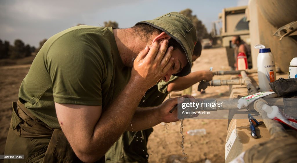 An Israeli soldier washes his face on the morning of July 28, 2014 near Kafar Azza, Israel. As Israel's operation 'Protective Edge' in Gaza continues, the international community struggles to find a truce agreement.