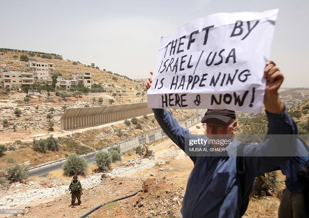 An Israeli soldier watches a protester as Palestinian, Israeli and foreign peace activists protest against Israel's controversial separation barrier in the West Bank village of Beit Jala, near the biblical town of Bethlehem, on June 6, 2010.