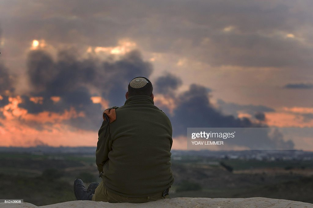 An Israeli soldier watches smoke billowing from Gaza following an Israeli airforce strike on January 11 , 2009. Tanks and warplanes pounded Gaza City before dawn on Sunday, hours after Israel warned it would escalate its war on Hamas targets, as the death toll in the 16-day-old conflict passed 850. AFP PHOTO / YOAV LEMMER