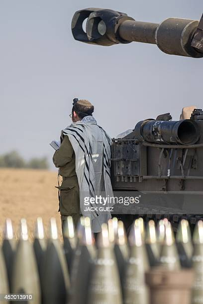 An Israeli soldier wearing a 'Talit' and 'Tefilin' performs morning prayers near a 155mm mobil artillery cannon along the southern Israeli border...