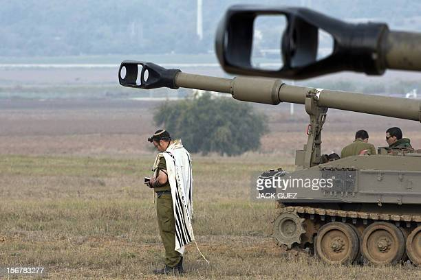 An Israeli soldier wearing a 'Talit' wraps the strap of his 'Tefilin' as he readies for morning prayers near his Israeli 155mm artillery canon at an...