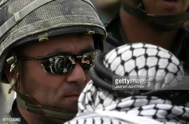 TOPSHOT An Israeli soldier wearing sunglasses looks at a Palestinian protester during a demonstration following Friday prayers in solidarity with...