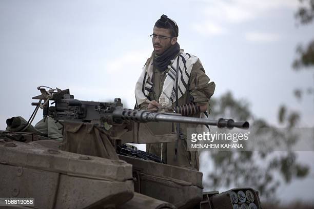 An Israeli soldier wearing 'Tallit' and 'Tefilin' performs morning prayers at an army deployment area near the IsraelGaza Strip border on November 22...