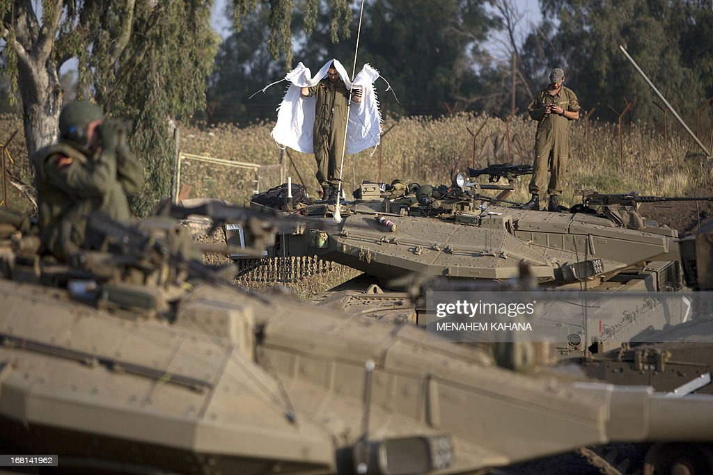 An Israeli soldier wears a Jewish prayer shawl as he pray on top of a Merkava tank deployed in the Israeli annexed Golan Heights near the border with Syria, on May 6, 2013. UN chief Ban Ki-moon has appealed for restraint after Israeli air strikes on targets near Damascus which prompted Syrian officials to warn 'missiles are ready' to retaliate. AFP PHOTO/MENAHEM KAHANA
