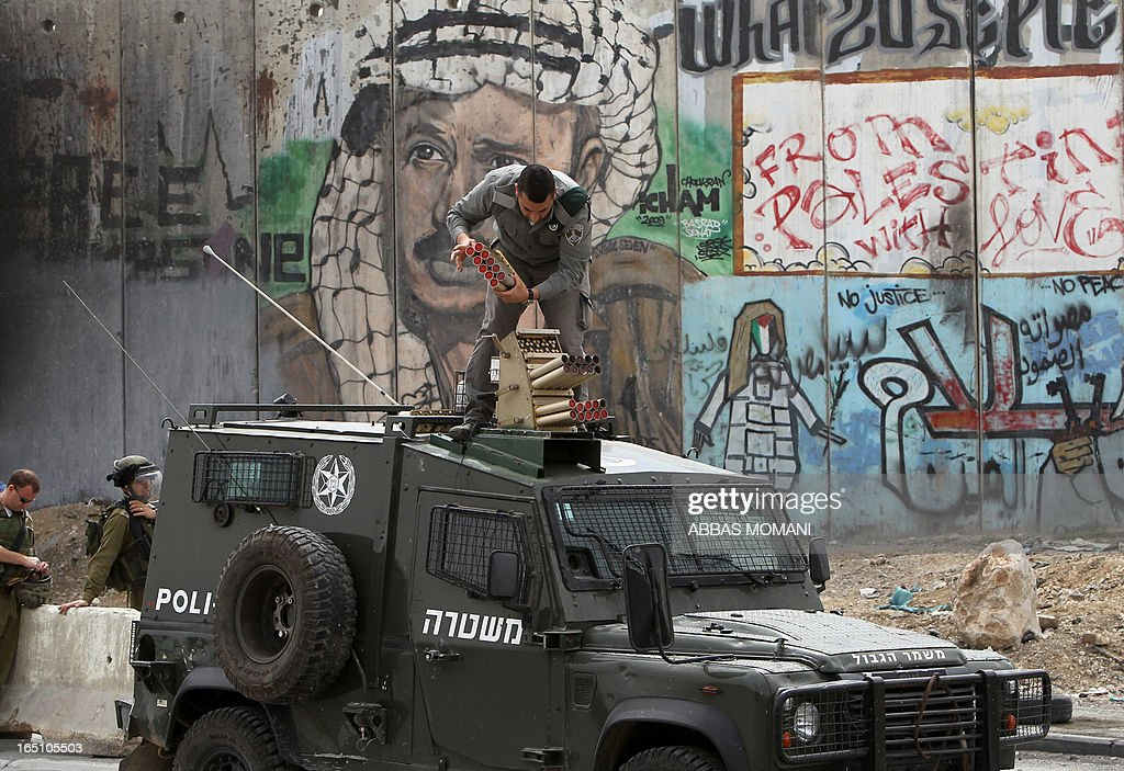 An Israeli soldiers prepares to fire tear gas on the top of his vehicle during clashes with Palestinians following a rally commemorating the 37th anniversary of 'Land Day', on March 30, 2013 near the Qalandia checkpoint in the Israeli occupied West Bank. Nearly 200 Palestinians clashed with Israeli forces in Qalandia, who responded with tear gas. Background is the Israeli separation barrier covered with grafittis. AFP PHOTO/ ABBAS MOMANI
