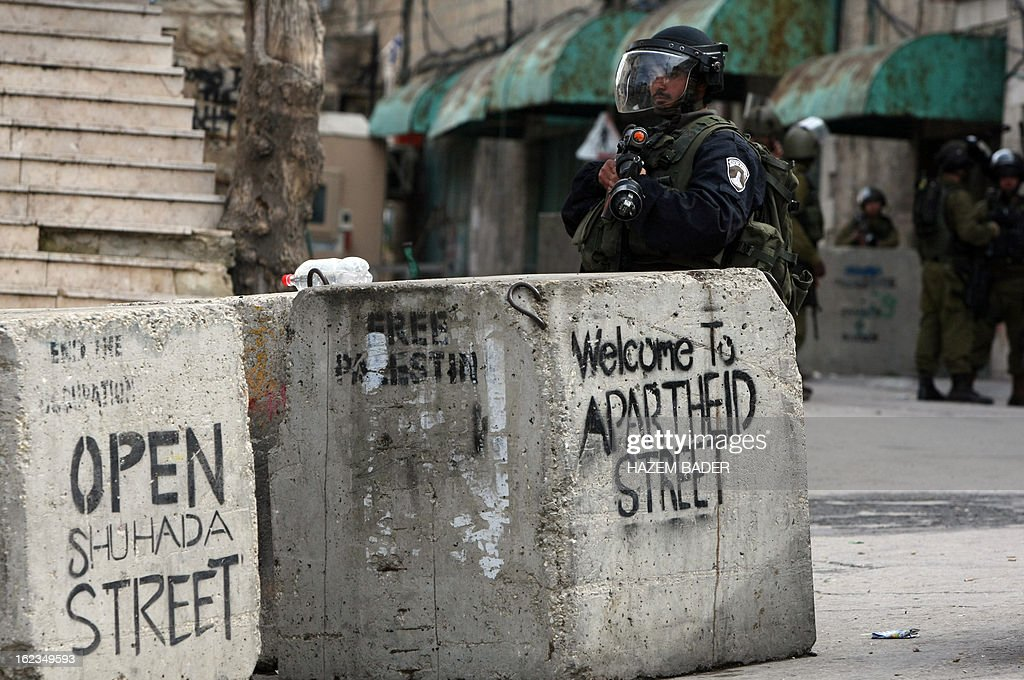 An Israeli soldiers stands behind a concrete block with graffiti sprayed on its sides in al-Shuhada street during clashes with Palestinian protestors who are demanding the right of access to the street that can only be used by Israeli settlers, in the West Bank town of Hebron on February 22, 2013. AFP PHOTO / HAZEM BADER