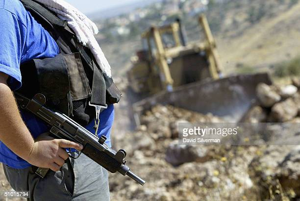 An Israeli stands guard with an Uzi submachine gun as a bulldozer cuts the path of Israel's separation fence July 1 2004 in the West Bank village of...