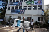 An Israeli student of the Blich high school carries a poster of former Likud minister Moshe Kahlon as he walks past posters of Tzipi Livni and Isaac...