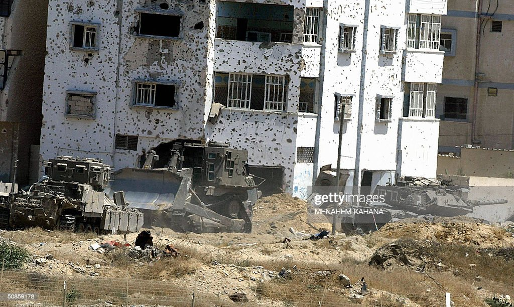 An Israeli tank and bulldozer move next to a bullet-riddled Palestinian building in the outskirts of the southern Gaza Strip town of Rafah 20 May 2004, on the third day of the massive Israeli army operation in the area. A total of 41 Palestinians have been killed since the Israeli army launched the Rafah raid early 18 May, dubbed 'Operation Rainbow' and aimed at stopping arms smuggling from Egypt through cross-border tunnels.
