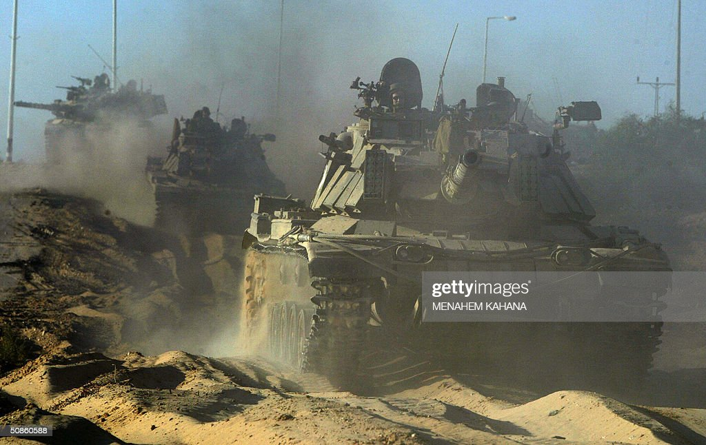 An Israeli tank convoy towards the outskirts of the southern Gaza Strip town of Rafah 20 May 2004, on the third day of the massive Israeli army operation in the area. A total of 41 Palestinians have been killed since the Israeli army launched the Rafah raid early 18 May, dubbed 'Operation Rainbow' and aimed at stopping arms smuggling from Egypt through cross-border tunnels. AFP PHOTO /Menahem KAHANA