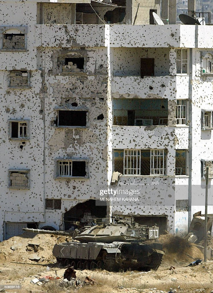 An Israeli tank moves next to a bullet-riddled Palestinian building in the outskirts of the southern Gaza Strip town of Rafah 20 May 2004, on the third day of the massive Israeli army operation in the area. A total of 41 Palestinians have been killed since the Israeli army launched the Rafah raid early 18 May, dubbed 'Operation Rainbow' and aimed at stopping arms smuggling from Egypt through cross-border tunnels.