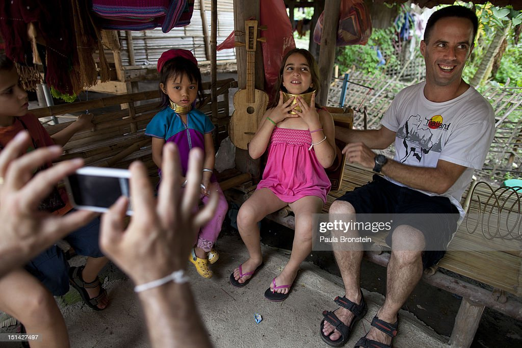 An Israeli tourist tries on a the heavy long neck gold band while her family takes a photo at the Baan Tong Luang Hiill tribe village on September 4, 2012 in Maerim, Thailand. Baan Tong Luang is a fabricated village containing 6 separate Thai Hill Tribes where visitors are expected to pay $16 or 500 Thai bhat for the entrance fee. Some of the ethnic tribes include the Lahu, Hmong, White Karen, Long necked Karen, Yao, and Akha. The village opened in 2005 attempting to preserve the old traditions of the ethnic Hill Tribe, while providing an income for them. Visitors must pay an entry fee of 500 Thai that or $16. Life for many of Thailand's Hill Tribe population can be difficult since it can be hard for them to make a living. Their language, costume and culture are different along with the frequent legal problems over Thai citizenship. Hill tribe is a term used in Thailand for all of the various tribal peoples who migrated from Tibet, or elsewhere in China over the past few centuries.