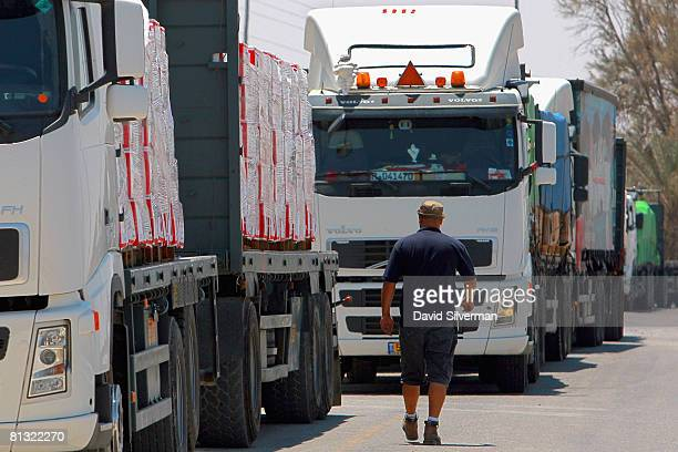 An Israeli trucker walks past heavygoods vehicles parked on the roadside as Israeli farmers block the road to vehicles carrying food and supplies to...