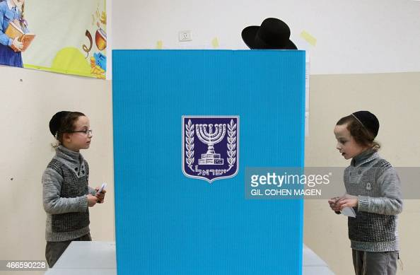 An Israeli ultraorthodox Jewish man accompanied by his children prepares to cast his ballot at a polling station in Bnei Brak near the city of Tel...