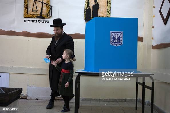 An Israeli ultraorthodox Jewish man and his daughter walk to cast his ballot at a polling station in Jerusalem on March 17 2015 Israelis are voting...