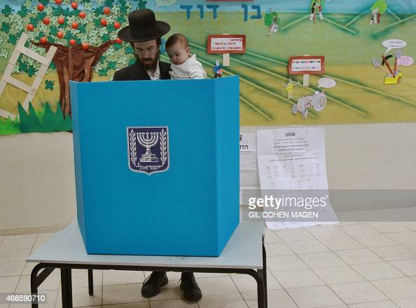 An Israeli ultraorthodox Jewish man carries his baby as he prepares to cast his ballot at a polling station in Bnei Brak near the city of Tel Aviv on...