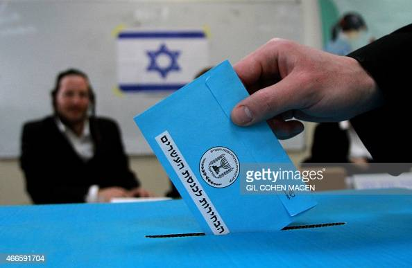An Israeli ultraorthodox Jewish man casts his ballot at a polling station in Bnei Brak near the city of Tel Aviv on March 17 2015 Israelis are voting...