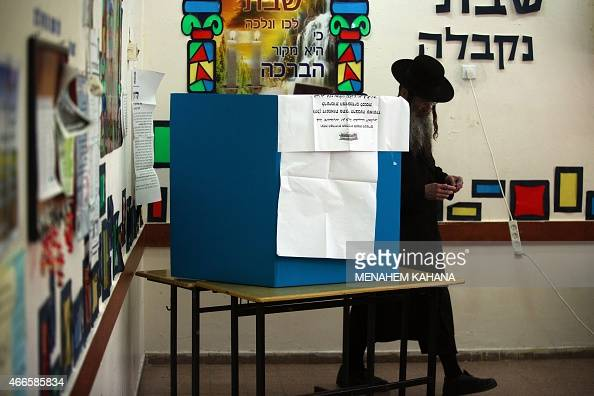 An Israeli ultraorthodox Jewish man leaves the voting booth before casting his ballot at a polling station in Jerusalem on March 17 2015 Israelis are...
