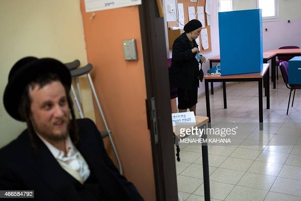 An Israeli ultraorthodox Jewish woman casts her ballot at a polling station in Jerusalem on March 17 2015 Israelis are voting in a closefought...