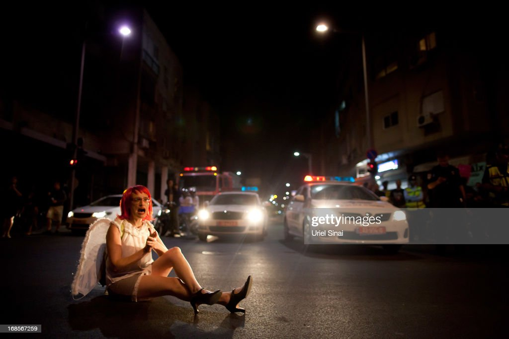 An Israeli woman blocks a main road as demonstrators march through the streets to protest against Israeli Finance Minister Yair Lapid's budget cuts on May 11, 2013 in Tel Aviv, Israel. Thousands of Israelis took to the streets to protest against austerity measures presented this week as part of the state's new budget.
