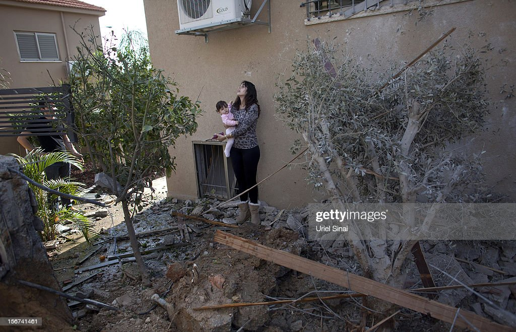 An Israeli woman carries a child outside her house after it was hit by a rocket fired from the Gaza Strip on November 20, 2012 in Beersheba, Israel. Hamas militants and Israel are continuing talks aimed at a ceasefire as the death toll in Gaza reaches over 100 with three Israelis also having been killed by rockets fired by Palestinian militants.