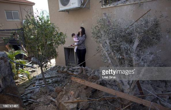 An Israeli woman carries a child outside her house after it was hit by a rocket fired from the Gaza Strip on November 20 2012 in Beersheba Israel...