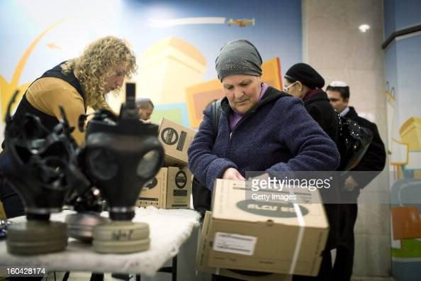 An Israeli woman collects gas mask kits from a distribution station in a shopping mall January 31 in Pisgat Ze'ev East Jerusalem Israel Israel...