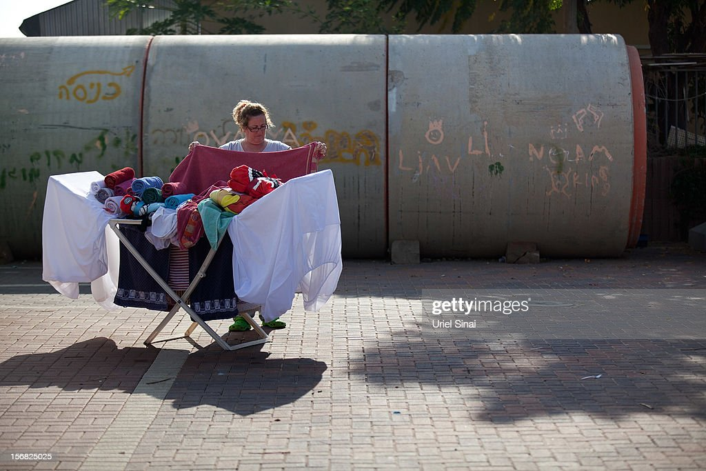An Israeli woman does her laundry outside her house and next to a large concrete pipe used as a bomb shelter on November 22, 2012 in Nitzan, Israel. The ceasefire between Israel and Hamas appears to be holding despite rockets being fired from Gaza. During the night the IDF reportedly arrested a number of 'terror operatives' in the West Bank in continued efforts to restore peace in the region.