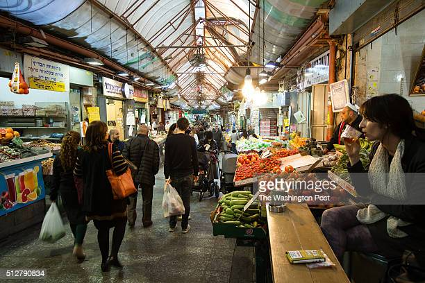An Israeli woman drinks beer at a bar as shoppers walk through the Mahane Yehuda Market often called 'The Shuk' on February 24 in Jerusalem Israel...