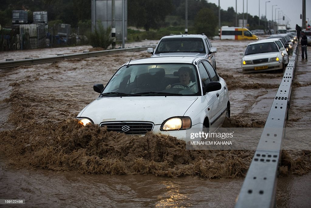 An Israeli woman drives her car in a flooded road near the Israeli-Arab town of Kfar Qara, in central Israel, on January 8, 2013. Stormy weather, including high winds and heavy rainfall, lashed Israel and the Palestinian territories, downing powerlines and trees and blocking roads causing several injuries. AFP PHOTO/MENAHEM KAHANA