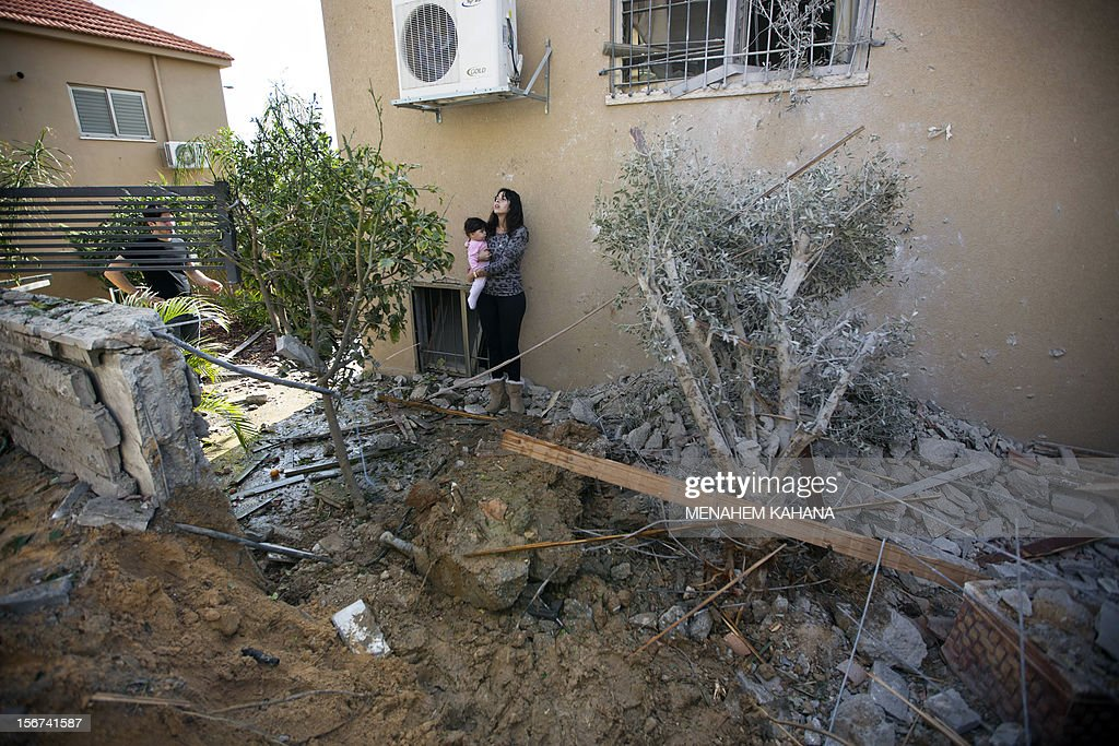 An Israeli woman holds a baby as she stands in the garden of her damaged home after it was hit by a rocket launched by Palestinian militants from the Gaza Strip in the southern Israeli city of Beer Sheva on November 20, 2012. Israel put on hold its threatened Gaza ground offensive to give Egyptian-led truce talks a chance as top diplomats flew in to boost efforts to end nearly a week of cross-border violence.