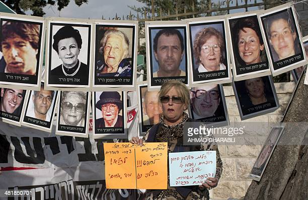 An Israeli woman holds signs in front of pictures of Israelis who were killed by Palestinians militants near a protest tent against the release of...