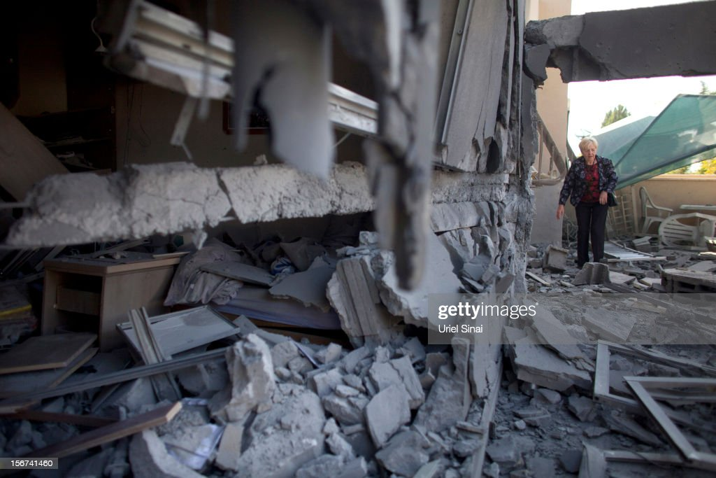 An Israeli woman inspects her house after it was hit by a rocket fired from the Gaza Strip on November 20, 2012 in Beersheba, Israel. Hamas militants and Israel are continuing talks aimed at a ceasefire as the death toll in Gaza reaches over 100 with three Israelis also having been killed by rockets fired by Palestinian militants.