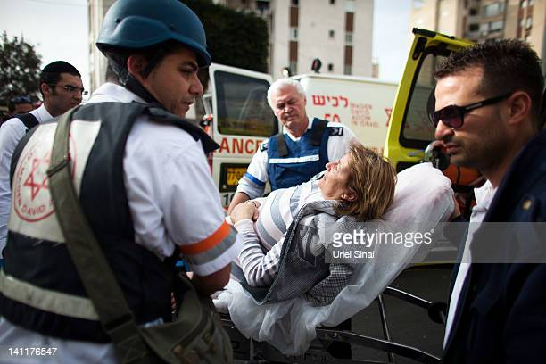 An Israeli woman is evacuated following a rocket attack from the nearby Gaza Strip on March 12 2012 in Ashdod Israel The UN and EU have appealed for...