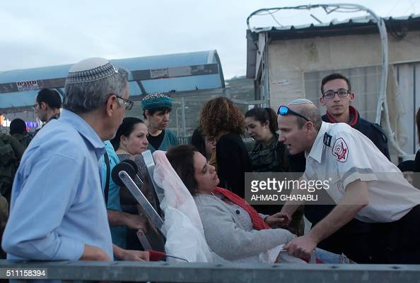 An Israeli woman is treated for shock outside the Rami Levi supermarket in Shaar Binyamin near Ramallah in the Israeli occupied West Bank after two...
