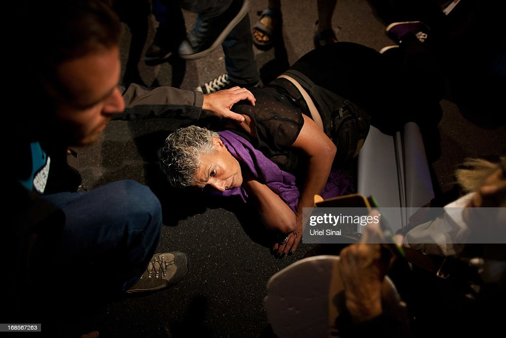 An Israeli woman is wounded on the ground after scuffling with the polce as demonstrators march through the streets to protest against Israeli Finance Minister Yair Lapid's budget cuts on May 11, 2013 in Tel Aviv, Israel. Thousands of Israelis took to the streets to protest against austerity measures presented this week as part of the state's new budget.