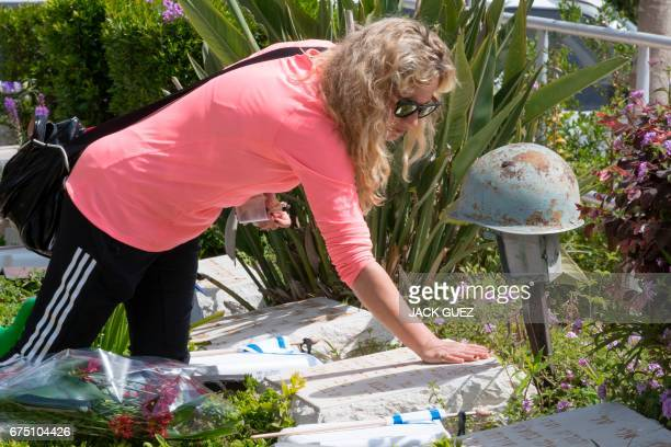 An Israeli woman mourns at the grave of a relative at the Kiryat Shaul military cemetery as the country starts to mark the memorial day for fallen...