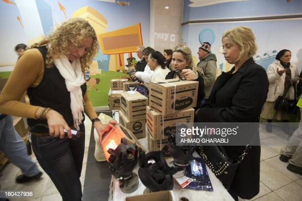 An Israeli woman picks up gas masks from a distribution center at a shopping center in Pisgat Zeev in East Jerusalem on January 31 2013 Syria's...