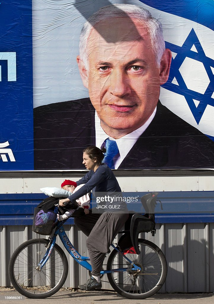 An Israeli woman ride her bike with a baby past an election campaign poster for Israeli Prime Minister Benjamin Netanyahu on January 18, 2013 in the Mediterranean coastal city of Tel Aviv ahead of the country's general elections on January 22. AFP PHOTO / JACK GUEZ