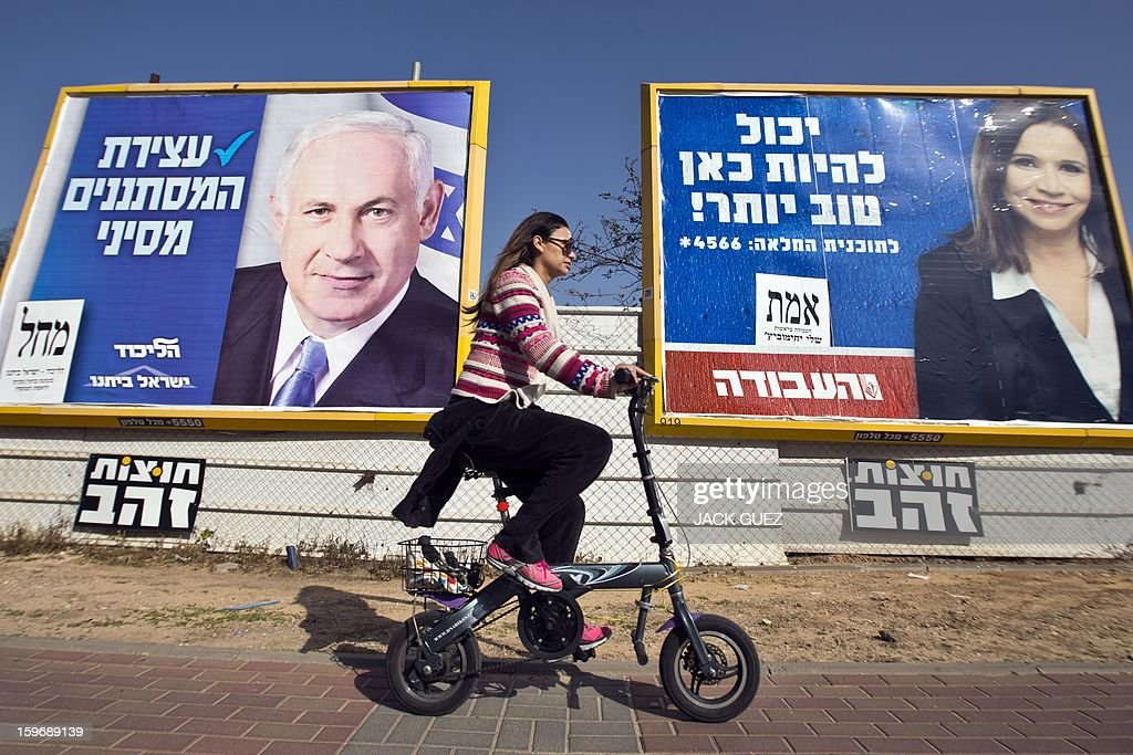 An Israeli woman rides her bicycle past election campaign posters for Israeli Prime Minister Benjamin Netanyahu (L) and Israeli Labor party leader Shelly Yachimovich (R) on January 18, 2013 in the Mediterranean coastal city of Tel Aviv ahead of the country's general elections on January 22.